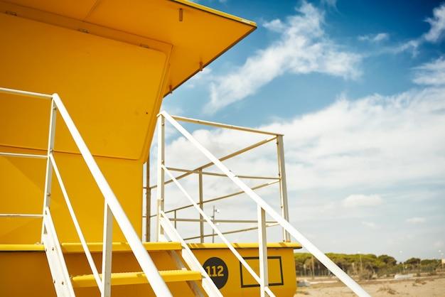 黄色いライフガードポストオン空のビーチ