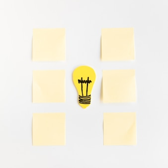 Yellow light bulb between adhesive notes arranged in a row