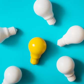 Yellow light bulb among the white bulbs on blue background