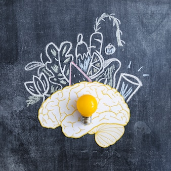 Yellow light bulb on brain with drawn vegetables on blackboard