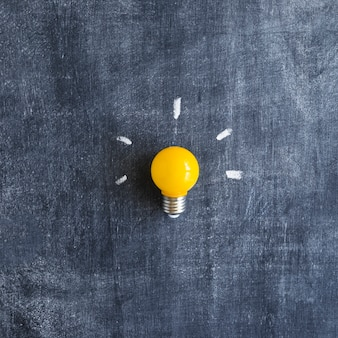 Yellow light bulb on chalkboard