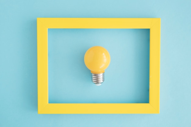 Yellow light bulb frame on blue backdrop