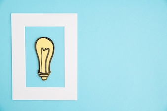 Yellow light bulb inside the white frame on blue backdrop