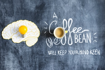 Yellow light bulb on brain paper cutout and coffee cup with text on chalkboard
