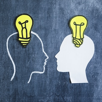 Yellow light bulb over the head of outline and white paper cutout face on chalkboard