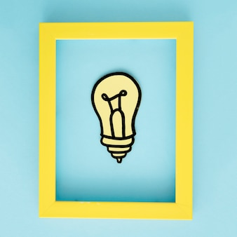 Yellow light bulb paper cutout with yellow border frame on blue background