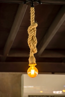 Yellow light bulb the sphere hanging with a rope.