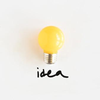 Lampadina gialla con testo idea su sfondo bianco