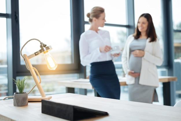 Желтый свет. крупный план маленькой яркой лампы, закрепленной на столе, в то время как коллеги радуются беседе