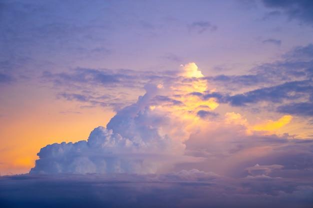 Yellow light of sunset behind big cloud on twilight sky, beautiful dramatic cloudy sky like heaven