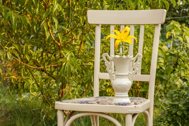 Yellow lily flower in porcelain vase on old chair staying in thegarden. outdoor hobbies and leisure theme.