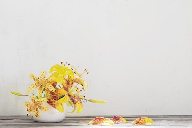 나무 테이블에 세라믹 흰색 꽃병에 노란색 백합