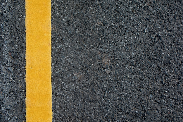 Yellow line on black asphalt road background with copy space