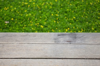 Yellow little flower on green grass with wooden background