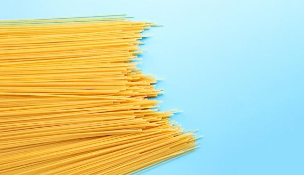 青い表面に黄色の長いスパゲッティ