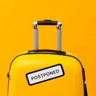 Yellow luggage with postponed sign