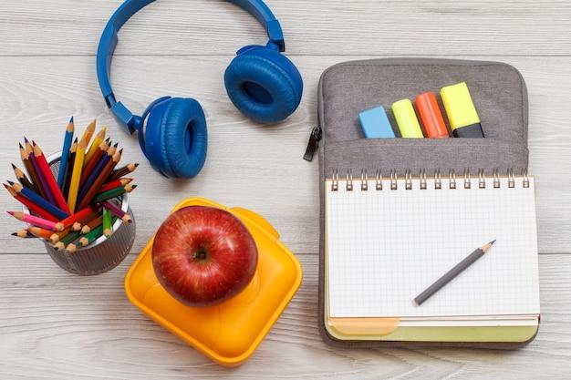 Желтый ланч-бокс, яблоко, цветные карандаши, наушники и открытая тетрадь на сумке-пенале с цветными фломастерами и маркером на серых деревянных досках. вид сверху. снова в школу концепции. школьные принадлежности.