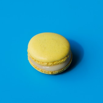 Yellow macaroon on blue background