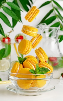 Yellow macaroons falling into the glass bowl. french dessert concept