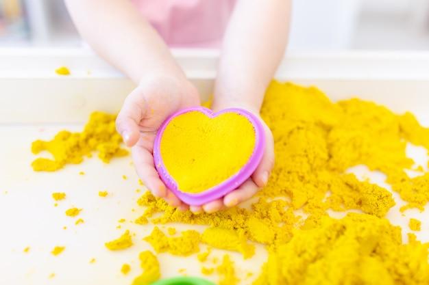 Желтый волшебный песок в форме сердц в руках детей на белом пространстве крупным планом. раннее сенсорное образование. готовимся к школе. развитие