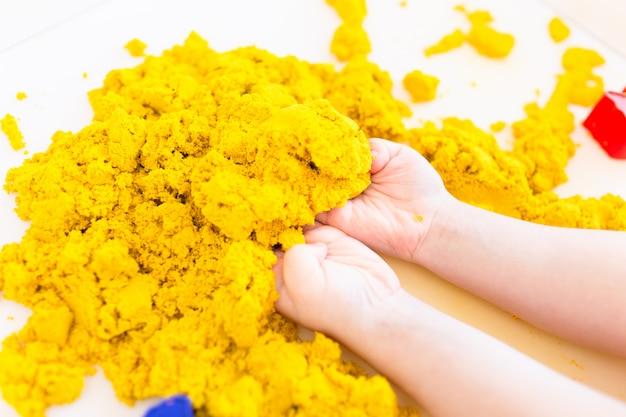 Желтый волшебный песок в руках детей на конце белого космоса вверх. раннее сенсорное образование. готовимся к школе. развитие