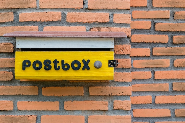 Yellow mailbox on brick home wall background