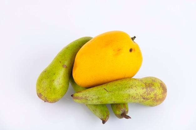 黄色いマンゴーの実、白い壁に緑の洋ナシ。スペースをコピーします。