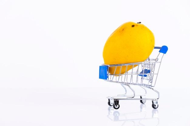 白い壁に、買い物かごに入った黄色いマンゴー。スペースをコピーします。