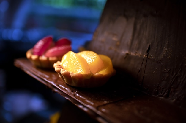 Yellow mango and red strawberry fruit tarts on chocolate plate in bakery or pastry shop
