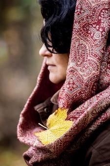 Желтый кленовый лист упал на платок женщины. женщина гуляет в осеннем лесу