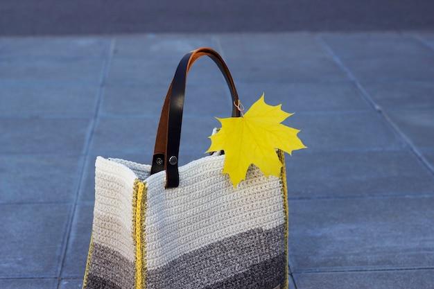 Желтый кленовый лист на вязаной серой сумке на улице города натюрморт с красками осени