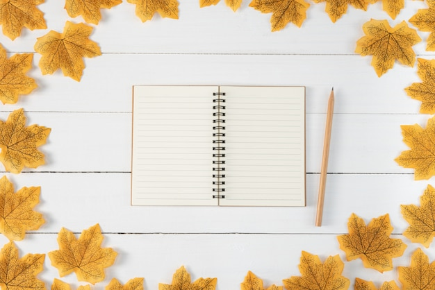 Yellow maple leaves, book and pencil on white wooden background. autumn, fall , top view, copy space.