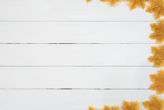 Yellow maple leaves on white wooden background. autumn, fall concept, top view, copy space.