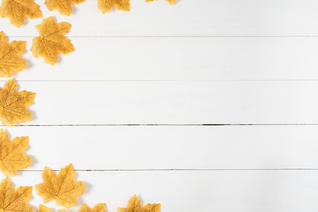 Yellow maple leaves on white wooden background. autumn, fall , top view, copy space.