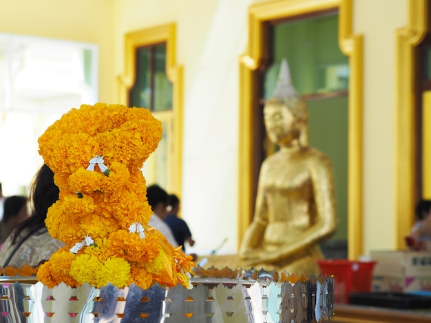 Yellow marigold garland flowers over blur background of buddhism people at temple in thailand.