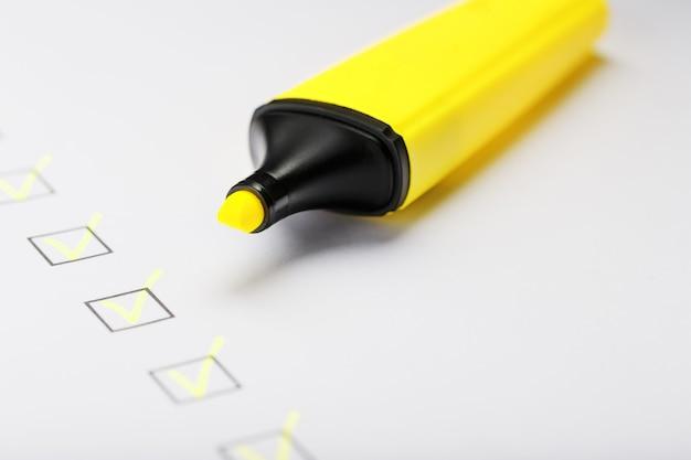 チェックリストシートにマーカーが付いた黄色のマーカー。チェックリストは、タスクの概念を完了しました。