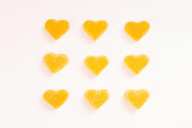 Yellow marmalade hearts in sugar on white background. marmalade sweets. copy space. view from above