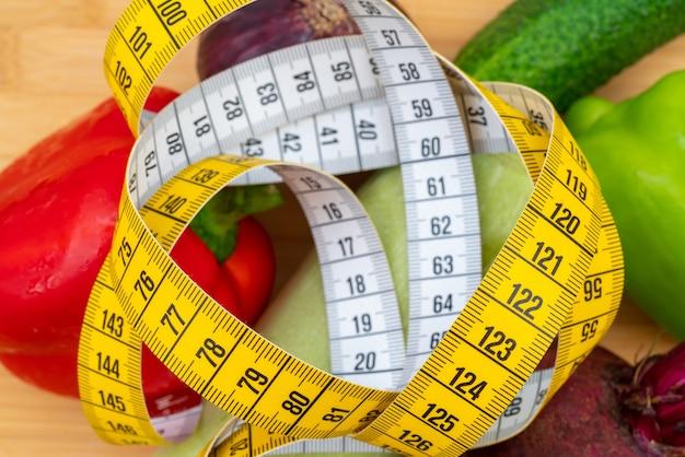 木製のまな板に黄色の巻尺と野菜。健康的なライフスタイルダイエット。