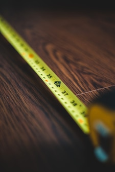 Yellow measuring tape on brown wooden table