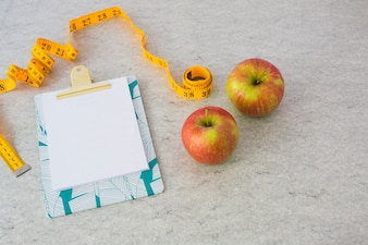 Yellow measuring tape; clipboard and apples on textured background