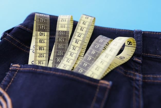 黄色の巻尺はジーンズのポケットのクローズアップにあります
