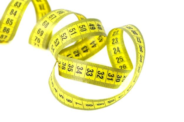 白い背景に分離された黄色の巻尺、健康生活