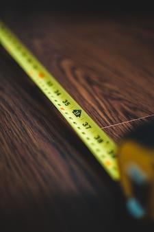 茶色の木製のテーブルに黄色の測定テープ