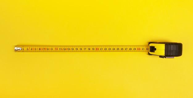 Желтая измерительная лента на желтом