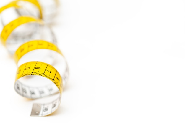 Yellow measuring tape on white background. measurement of length and circumference. lose weight and get fat.