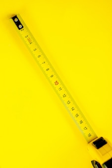 Yellow measuring tape on yellow background. copy space