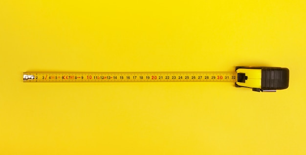 Yellow measuring tape on yellow