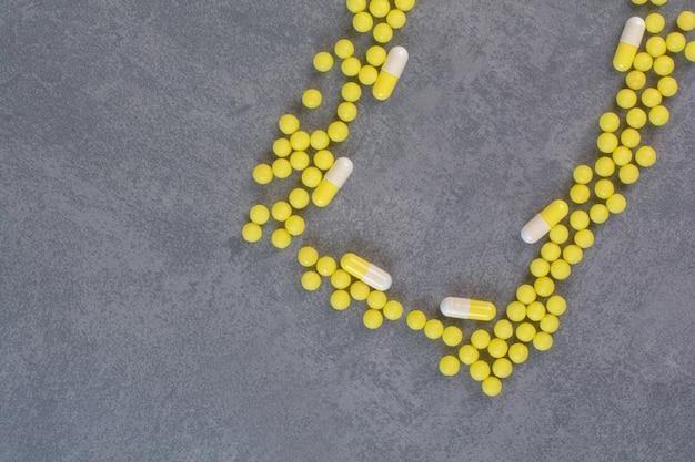 Желтые медицинские таблетки и капсулы на мраморном столе.