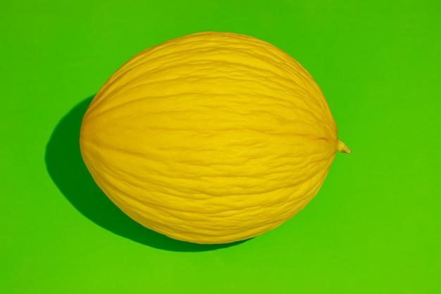 明るい緑の背景に黄色のメロン。食品のコンセプト。影のあるフラットレイ(すべての果物に焦点が当てられています)