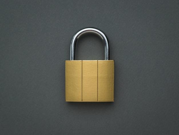 Желтый металлический замок на темно-сером фоне. понятие защиты и безопасности. плоская планировка.